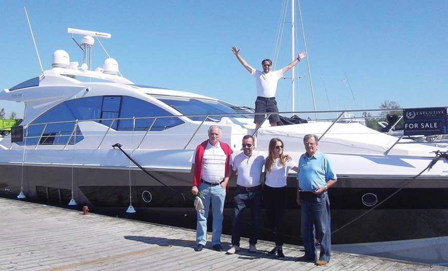 The Executive Yacht Canada team celebrates a new arrival earlier this spring.