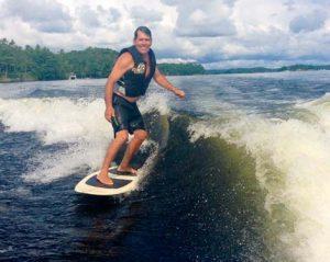 Ron wake surfing behind a friends boat in Muskoka, Ontario.